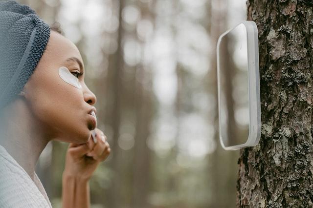 Czy pasta z węglem wybiela zęby oraz kobieta w ręczniku myjąca zęby na zewnątrz